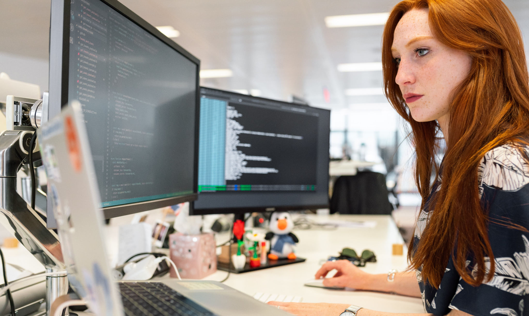 A woman sitting at a desk coding.