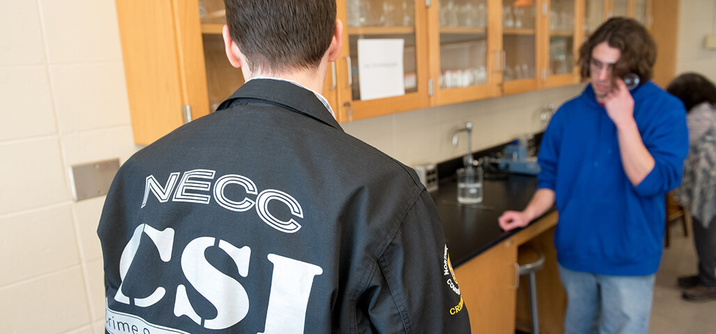 Several Criminal Justice: Private and Public Safety students in a science Laboratory. One is wearing an 'NECC CSI' jacket.