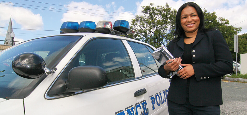 A Law Enforcement Certificate student stands, with books in hand, outside next to a police car.