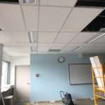 Interior of a Dimitry Building room with white ceiling tiles being installed around already inplace lighting fixtures, while the floor is still unfinished. The wall is painted (light blue with white trim).