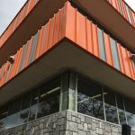 Corner of the bulding -looking up. Finished stone siding, orange and grey siding, and windows un-boarded.