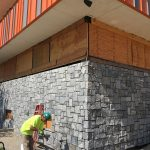 Dimitry renovations: Construction worker finishing the stone siding on the bottom building (corner of building)-08-27-2018