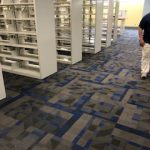 Inside the library with emply white bookcases on recently installed Carpet, which has modern geometric partters using squares and triagles of various shades from deep blue to dark grey.