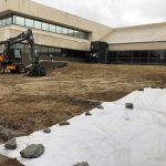 Dimitry building view of entrance and cleared landscape, with large excavatorin front, and white tarp covering part of the ground.