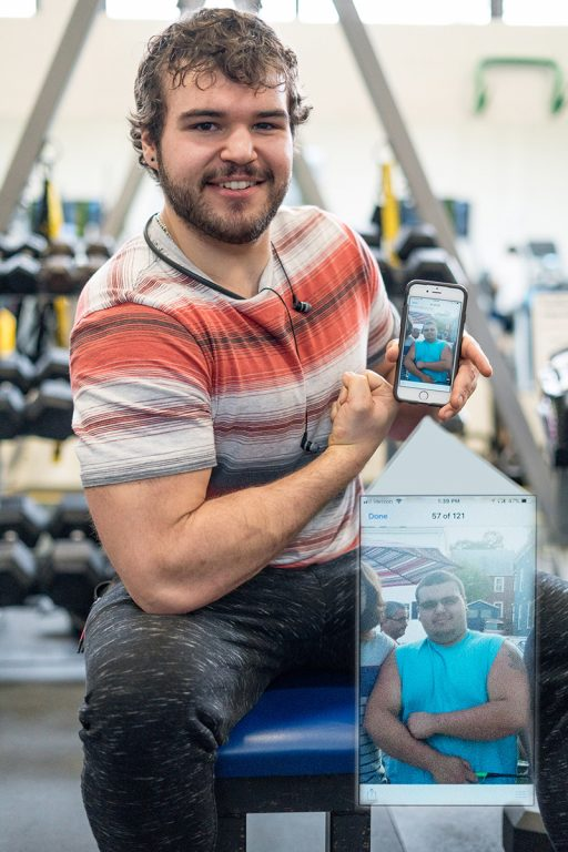 Adam Kinser, in the wellness center gym, holding up his phone with an image on it of himself when he weighed more.
