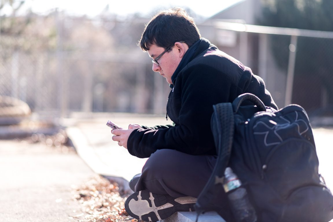 Brian Oppedisano, sitting on the ground outside, looking at his phone.