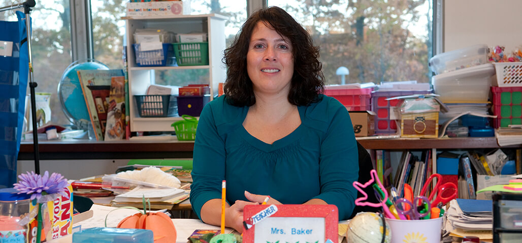 An Educational Studies student teacher in an elementary classroom surrounded by books and art supplies.