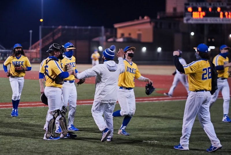 Baseball team wearing yellow and blue jerseys high-fiving one another