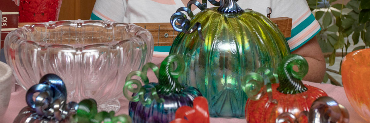 Colored glass pumpkins on table
