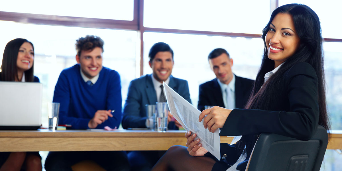 A business woman looking prepared and happy, sits at a table with four eager business people.
