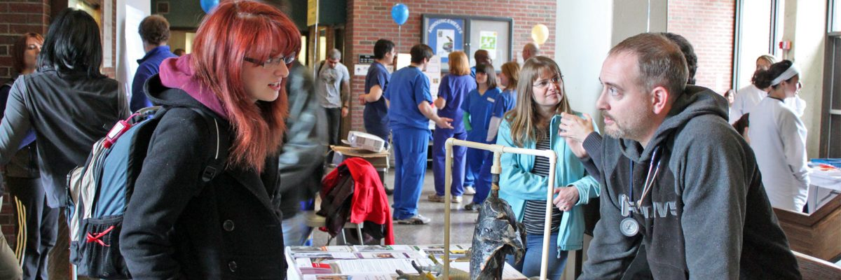 A student talks with a presenter at a table with a black lung on display, while various other people explore tables, resources, and talk to professionals.