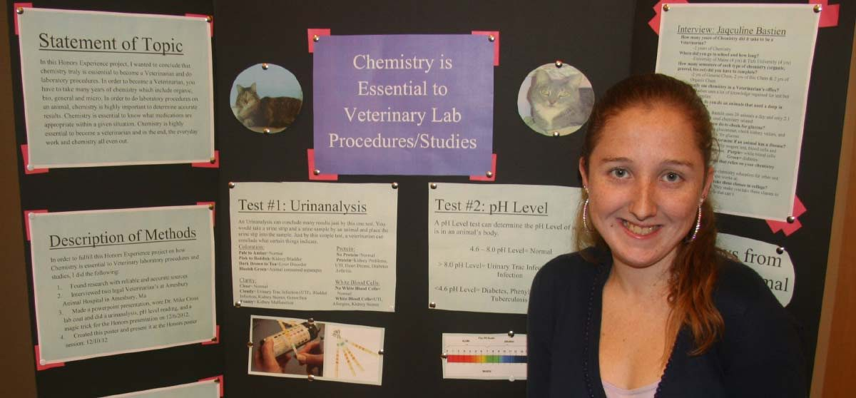 "Kelsey in front of a tri-fold poster with multiple papers and images about ""Chesitry is Essential to Veterinary Lab Procedure Studies""."