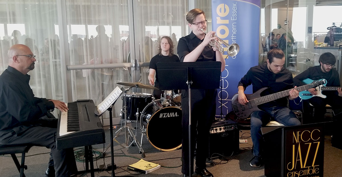 Four members of the Jazz Ensemble playing keyboard, trumpet, drums and 2 playing guitars.