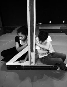 Two students each sit on the opposite side of a wall with a hand pressed against the wall as if they are connecting through it, and both students are looking down at the floor with a sad expression.