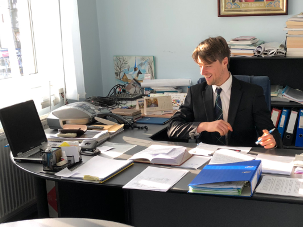 Dan sitting at his desk with organized piles of papers and tools on it, and an organized bookcase behind