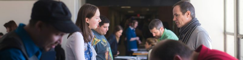 Prospective students talking with staff at an Open House Event.