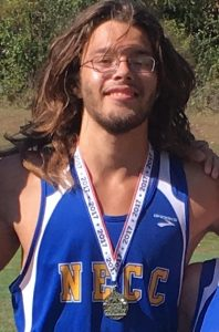 Ruben in his NECC athletics shirt wearing a medal around his neck.