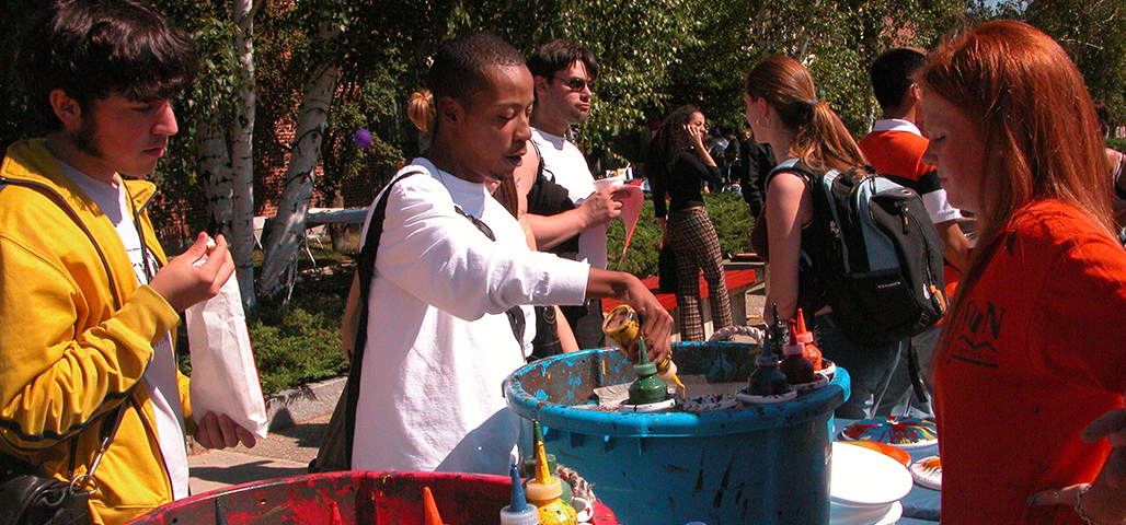 A student pours paint in a spin art machine, while another watches and muches on popcorn. Other students behind them walk toward other activities.