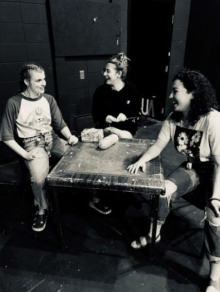 Three students sitting at a table rehearsing.