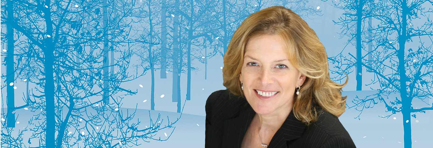 Karen Andreas in front of a wintery forest scene.