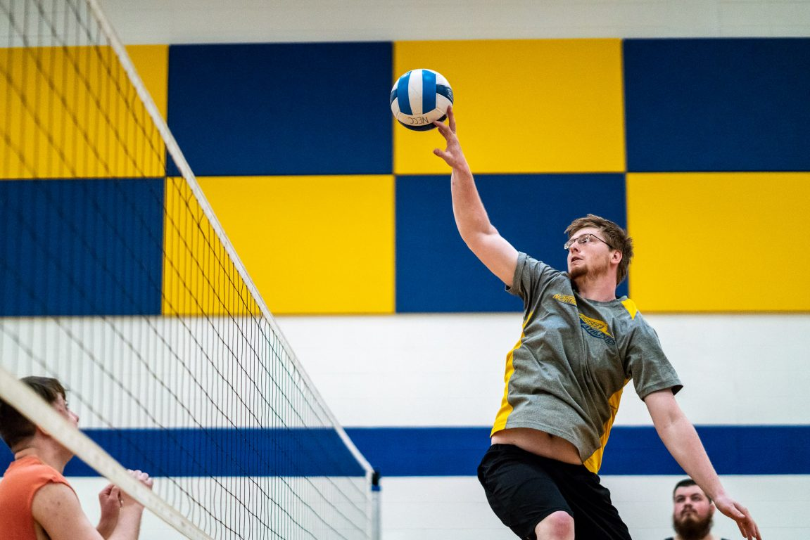 NECC student, Matthew Day leaps up to knock a volleyball over a net