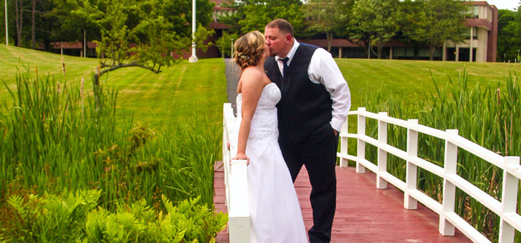 A bride and groom kiss while standing on a small wooden bridge