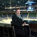 An alumna smiles at the camera, sitting and overlooking a large hockey arena