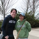 Two NECC alumni smile at the camera, wearing their 4-year college sweatshirts