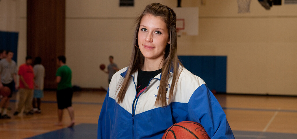 A female Exercise Science student on the basketball court.