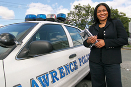 a criminal justice student stands in front of a police car