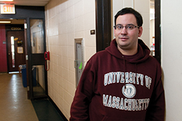 a young man in a UMass sweatshirt stands in a school hallway