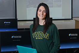 a young woman wearing a Lyndon State sweatshirt sits in a computer lab