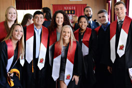 Nine Regis Bachelor graduates wearing their gown and Regis stole.