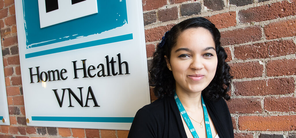 A medical billing certificate student standing outside the Home Health VNA building.