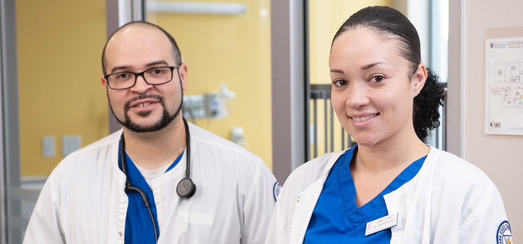 Two nursing students, one male, one female stand next to each other smiling.