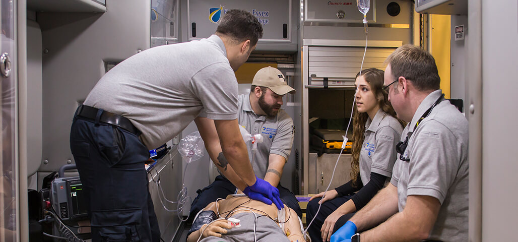 Four Paramedic Technology students working on a 'patient' in the ambulance simulation room, which is set up with equipment and technology like an ambulance.
