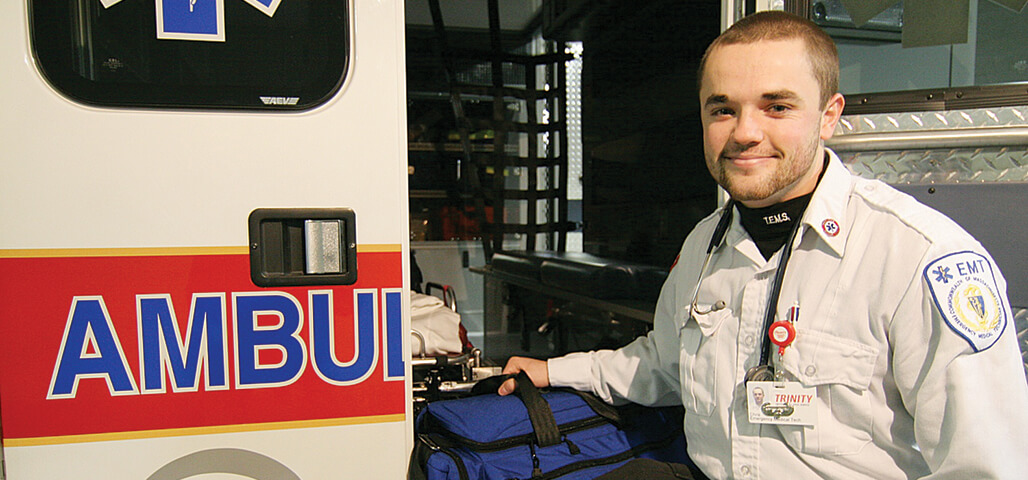 A Paramedic Technology  Assocaite degree student in EMT uniform, standing at the open door of a stocked ambulence.
