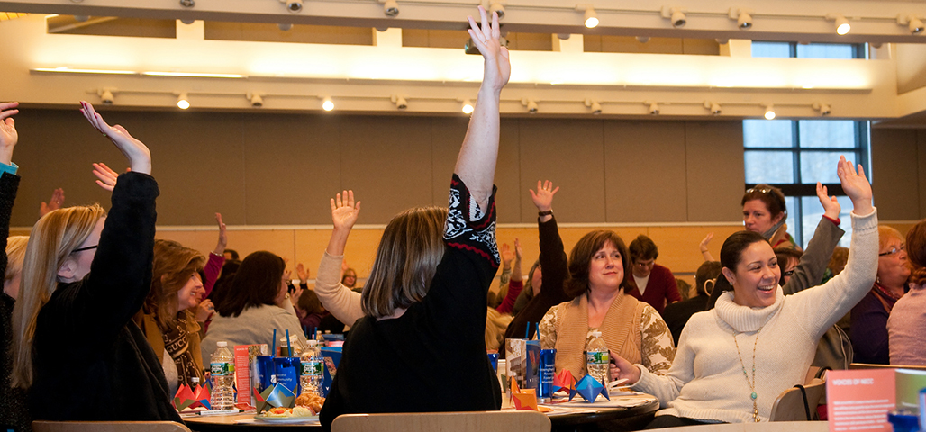 An Appreciative Inquiry meeting with many people seated at round tables, happy faces and several with hands raised.
