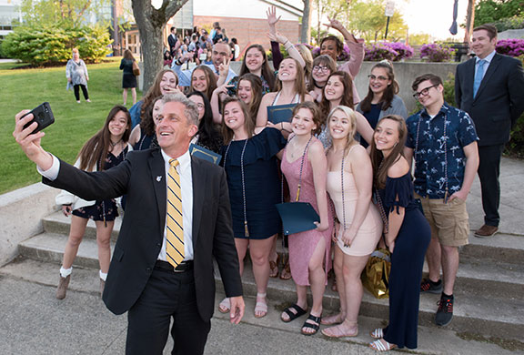 President Glenn holding up a cell phone with 19 early college students behind him.