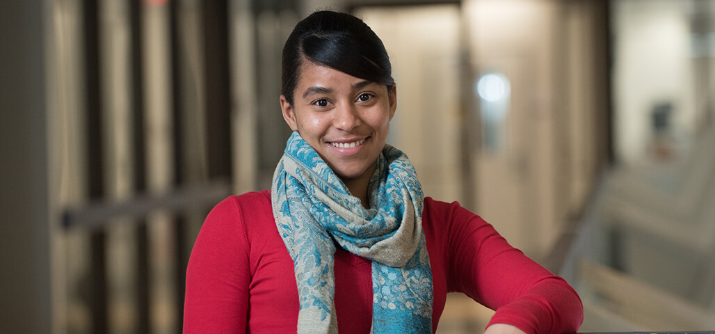 A young woman in the Liberal Arts: Psychology degree program, leaning her arm on a table and smiling.