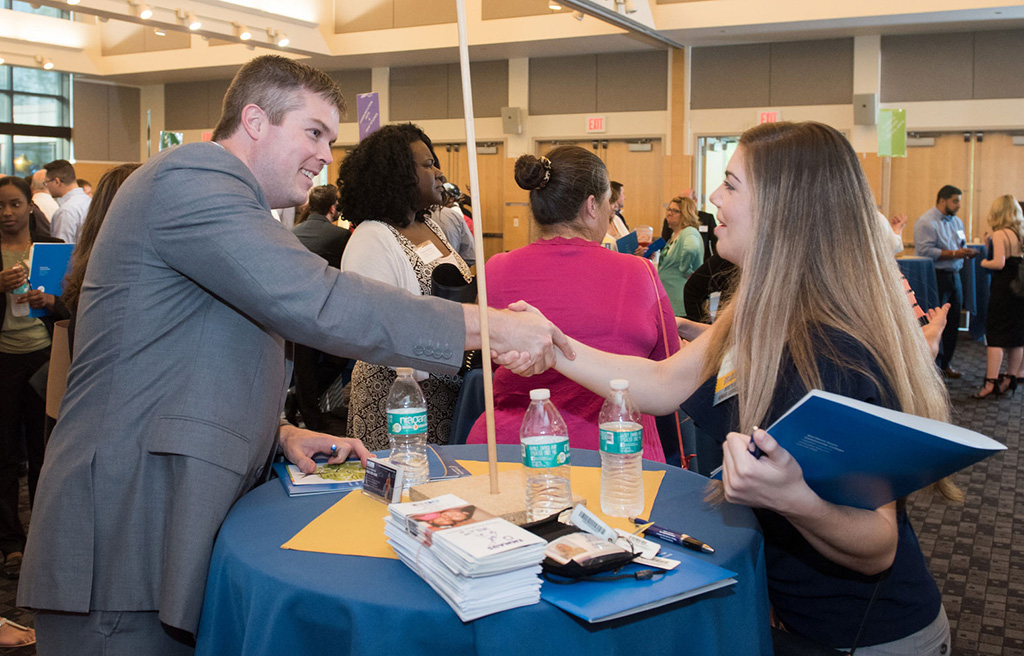 A young woman shakes hands with a business partner at a table