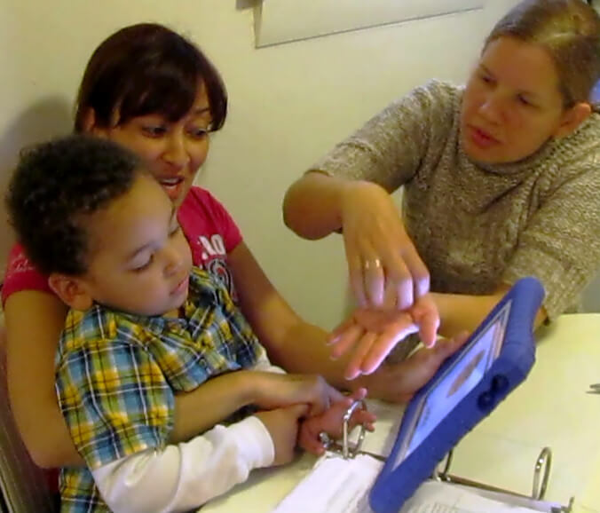 A boy, his mother, and a teacher are seated at a table. The boy is in his mother's lap. They are all looking at an iPad together. There is a picture of a cookie on the screen and the tutor is showing them the sign.