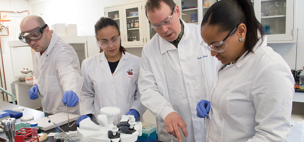 Three Laboratory Science degree students run testing under the close watch of a faculty member
