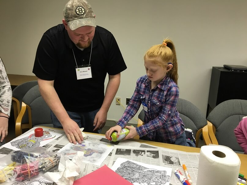 A young man and an elementary aged girl are standing together at a table, working on a craft. They are spraying something onto a piece of paper. There are markers, crayons and paper towels around them.