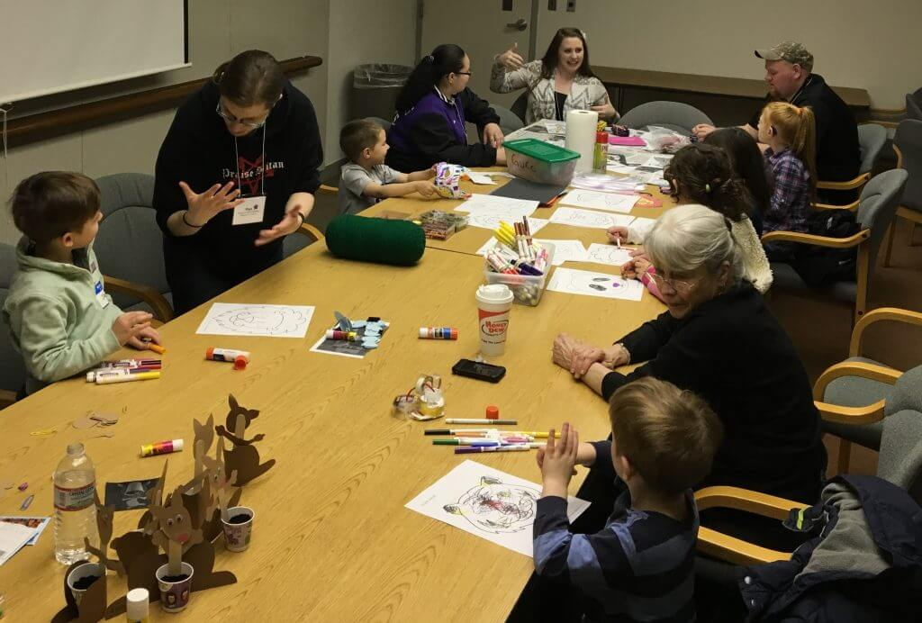 a group of adults and elementary aged children are sitting around a long table signing, and working on crafts together.