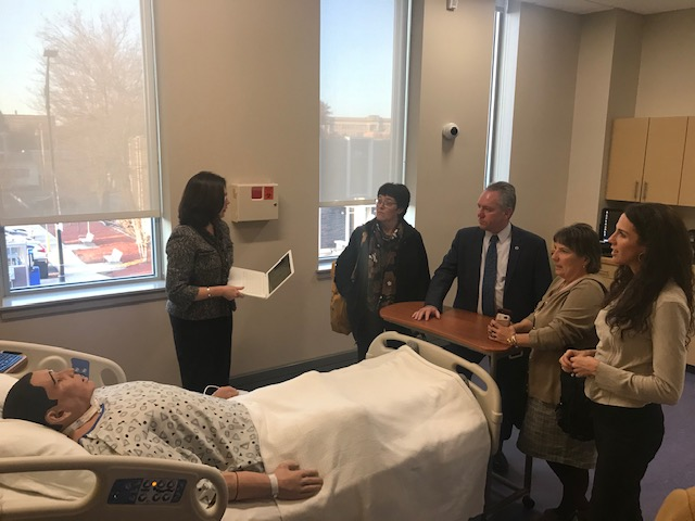 Massachusetts legislators tour the simulation lab and view how a simulation mannequin works.