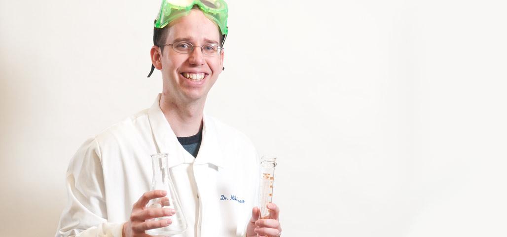 Mike Cross, a speaker in the NECC Speaker's Bureau, holding two chemistry flasks