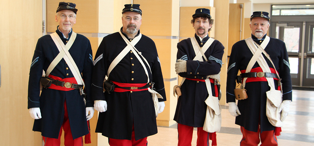 4 men dressed in civil war-era uniforms.
