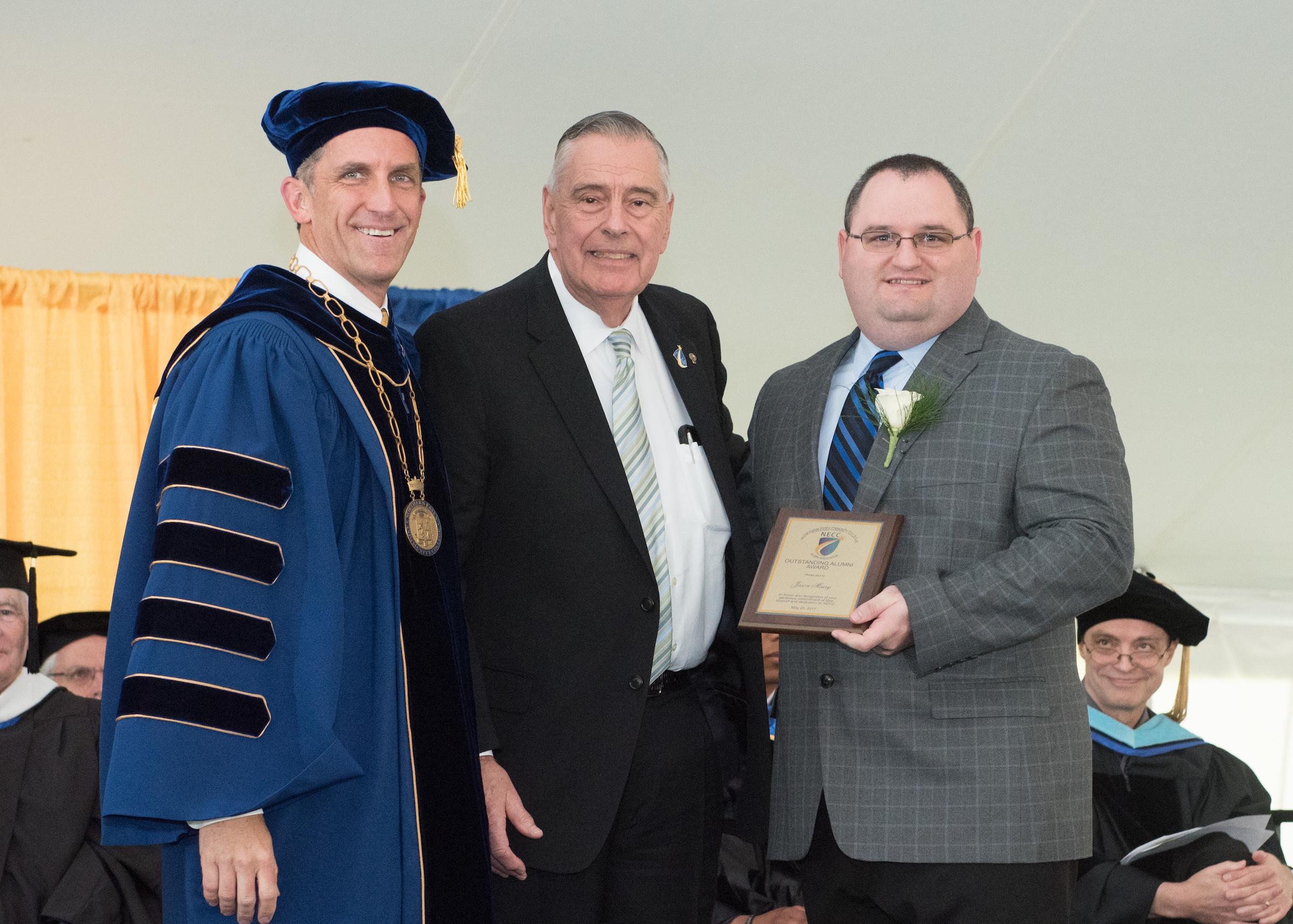 President Glenn in commencment regalia and Bill Klueber present Jason Moury the award.