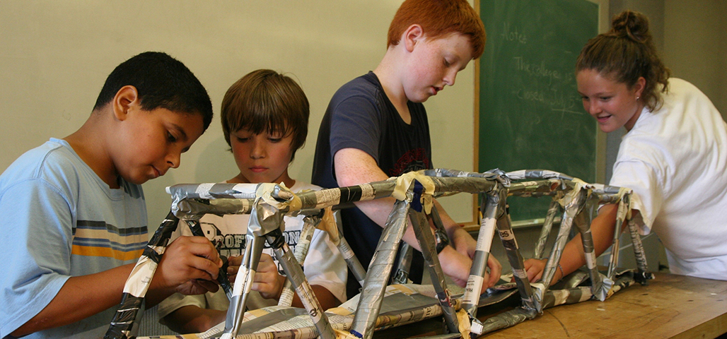 Four young boys in the college for kids program work together to construct a model bridge.